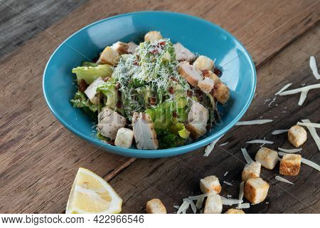 Chicken Cesar salad with croutons, grated cheese and lemon isolated on wooden rustic table