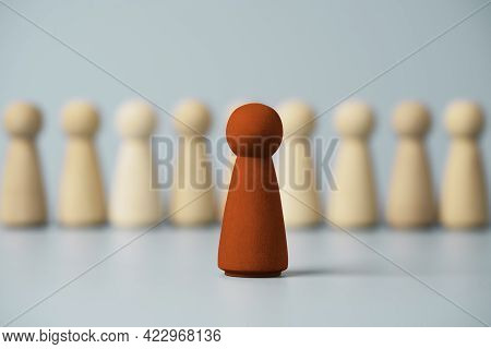 Red Wooden Figure Standing In Front Of Others Figures On Blue Background, Leadership And Management