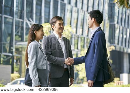 Asian Business Associates Meeting In The Street In Downtown Financial District Shaking Hands