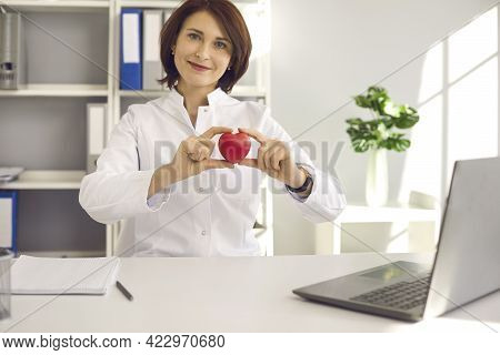 Portrait Of Female Cardiologist Holding Little Red Heart While Sitting At Desk In Office.
