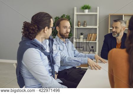 Young Company Manager Or Business Mentor Talking To Diverse Workers In Office Meeting