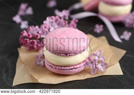Delicious Violet Macaron And Lilac Flowers On Black Table, Closeup