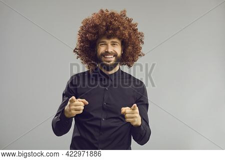 Toothy Smiling Confident Business Man In Funny Afro Hair Wig Pointing At Camera