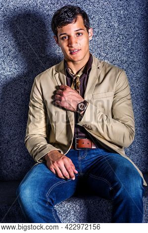 Young Man Fashion. A Young Man, Wearing A Beige Blazer, Blue Jeans, A Little Scarf, And A Wristwatch