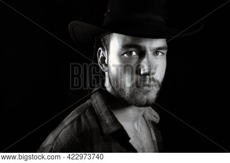 Portrait Of Handsome Male Cowboy Wearing Open Chequered Shirt And Hat Revealing Sixpack Abs Isolated