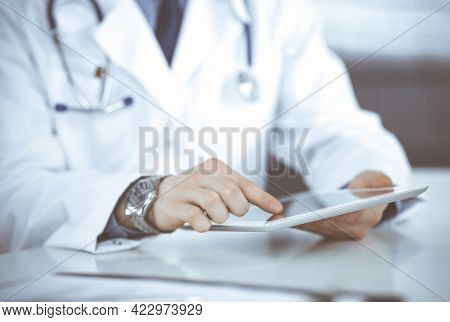 Unknown Male Doctor Sitting And Working With Tablet Computer In Clinic At His Working Place, Close-u