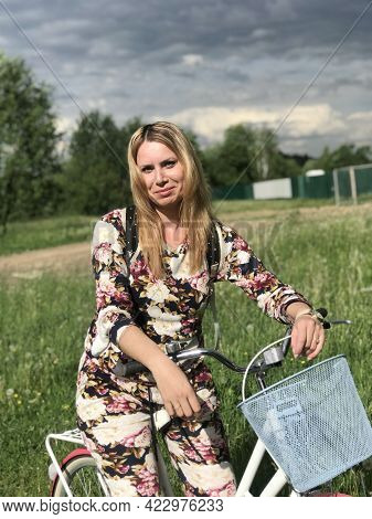 A Girl In A Tracksuit Posing On A Bicycle. Drinks Water From A Plastic Bottle. Stands Near The Raili