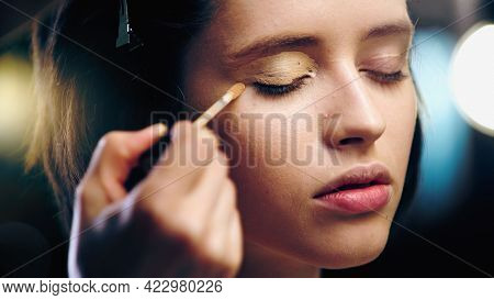 Makeup Artist Applying Concealer On Eyelid Of Model.