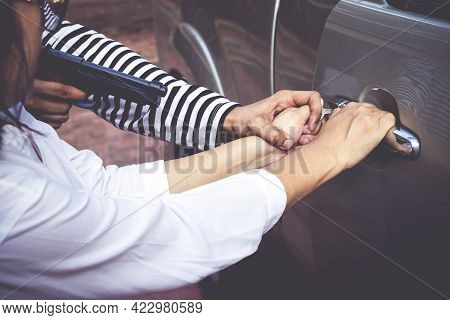 Car Thieves Hold A Gun To Rob A Car From A Woman Who Owns It. Close-up Photo. Insurance Concept. Pro