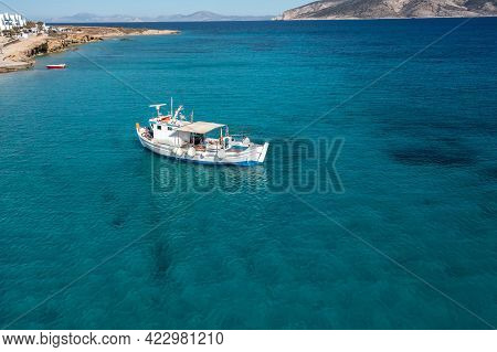 Greece, Cyclades. Aerial Drone View Of A Fishing Boat On Turquoise Color Sea Water