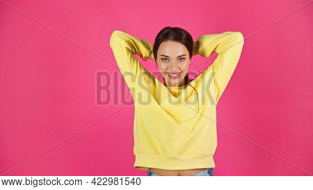 Smiling Young Adult Woman In Yellow Sweatshirt Adjusting Hair With Hands Isolated On Pink