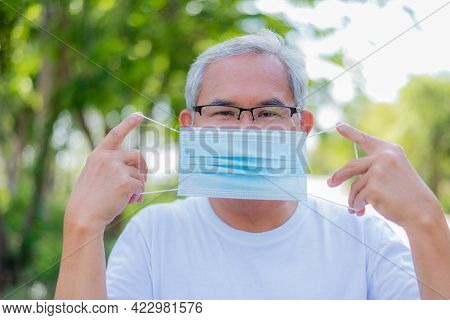 Old Asian Man Wearing A Face Medical Mask While Standing On The Roadside. Close-up Portrait.