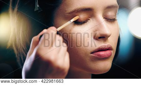 Makeup Artist Applying Concealer On Eyelid Of Young Woman.
