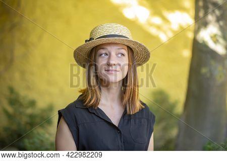 Street Portrait Of A 35-40-year-old Woman In A Summer Straw Hat On A Neutral Background, A Flirtatio