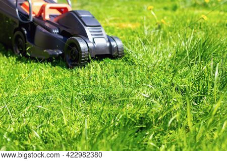 Selective Focus Of Green Grass In The Foreground And A Blurry Black Lawnmower In The Background