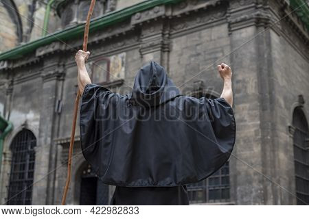 A Black-robed Monk With A Staff Stands In Front Of An Old, Gloomy Building With His Staff Held High.