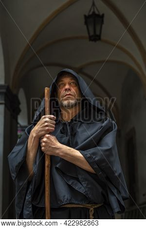 Portrait of an elderly monk 45-50 years old with a beard in a black robe with a staff, standing unde