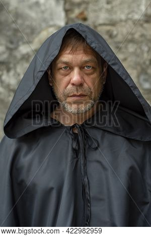 Portrait Of An Elderly Monk 45-50 Years Old With A Beard In A Black Robe With A Staff On The Backgro