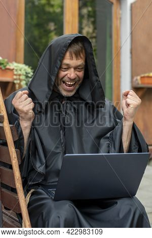 Portrait Of An Elderly Monk 45-50 Years Old In A Black Robe With His Hands Up, Sitting At A Laptop A