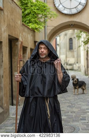 Portrait Of An Elderly Monk 45-50 Years Old With A Beard And A Black Cassock, Walking Down The Stree