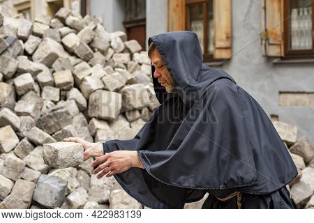 A Monk In A Black Robe Collects Paving Stones In A Pile Against The Background Of The Old City. Conc