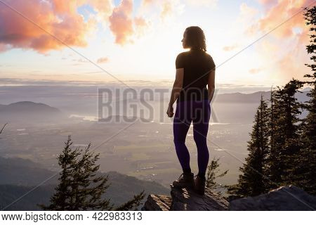 Adventurous Caucasian Adult Woman Hiking In Canadian Nature Over Looking Mountainous Landscape. Suns