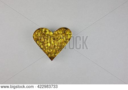 Yellow Capsules With Vitamin D3 On A Grey Background, Laid Out In The Shape Of A Heart. Healthy And