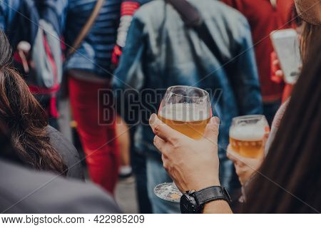 Hands Holding Glasses Of Beer On A Street, Selective Focus On The Foreground.