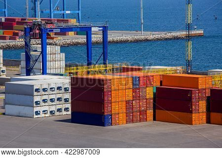 Container Fleet Of The Seaport With A Cargo Warehouse With A Folded Crane For A Pile Of Cargo Transp