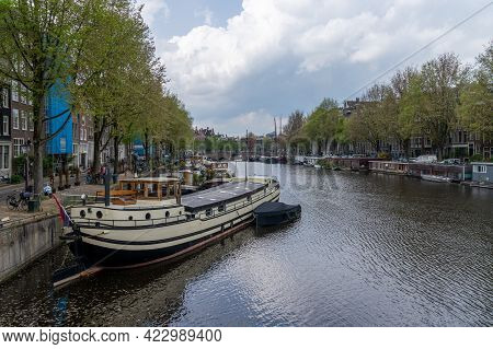 Cityscape View Of Amsterdam With Many Historic Buildings Lining The Sides Of The Amstel Canal