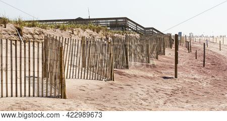 Wood Picket Fences In Front Of The Sand Dunes With A Wooden Walkway In The Distance Going Over The D