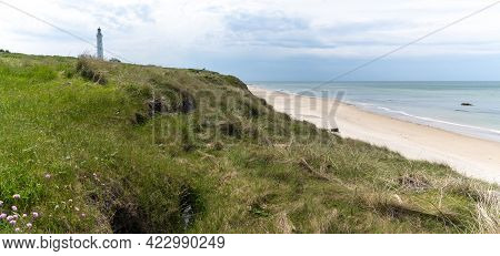 A Panorama Of The Lighthouse And Grassy Sand Dunes Above The White Sand Beach At Hirtshals In Northe