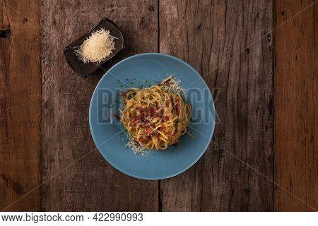 Top view of traditional Italian pasta dish, spaghetti carbonara with bacon, yolk, parmesan cheese on a plate isolated on wooden table