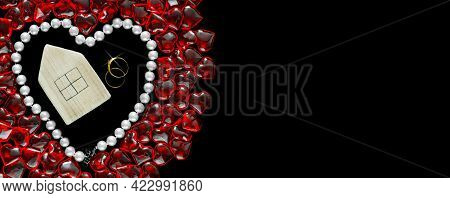 A Wooden House And Two Wedding Rings In A Heart Made Of White Pearl Beads Surrounded By Red Hearts I