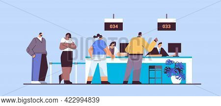 Mix Race People Looking At Display Number Board In Waiting Room With Ticket System Electronic Queuin