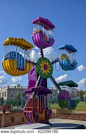Children's Attraction Is Quarantined Due To Covid-19. Colorful Ferris Wheel In Amusement Park On Blu