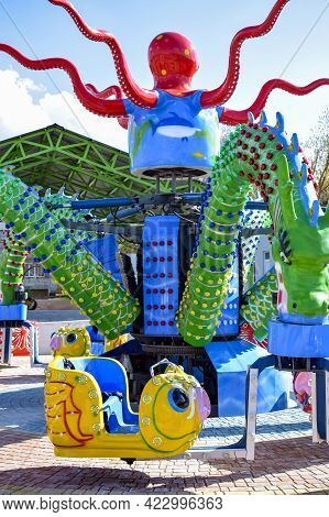 Children's Attraction Is Quarantined Due To Covid-19. Colorful Carousel In Amusement Park On Blue Sk