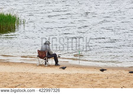 A Fisherman Sits On A Chair And Catches Fish With A Fishing Rod In The River. The Pigeons On The San