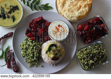 Vegetarian Meals Prepared In Kerala Style. The Serving Includes Boiled Red Rice, Lentil Curry, Stir