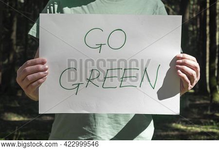 Go Green Words Written On Paper Poster In Male Hands In Forest.