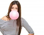 Portrait Of A Young Woman Blowing Bubblegum against a white background poster