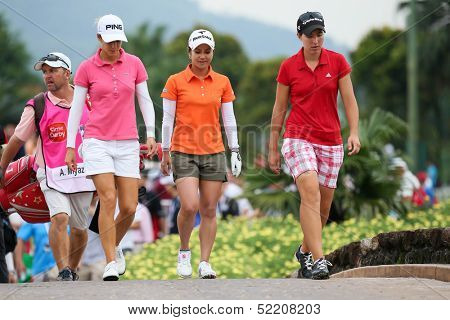 KUALA LUMPUR - OCTOBER 12: A. Munoz (left), A. Miyazato (mid) and C. Ciganda walk to the Hole 3 fairway of KLGCC course on Day 3 of the Sime Darby LPGA on October 12, 2013 in Kuala Lumpur, Malaysia.