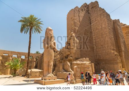 LUXOR, EGYPT - APR 10: Unidentified tourists at Statue of Ramesses II in Karnak temple of Luxor on 10 Apr 2013, Egypt. This was the largest temple complex of Amun-Re God in ancient  Thebes town.