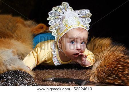Blue-eyed baby lying on fur litter near the hauberk and sword fox pelt in the background poster