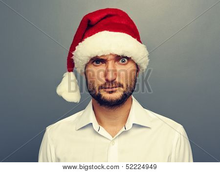 amazed man in santa hat looking at camera. photo over dark background