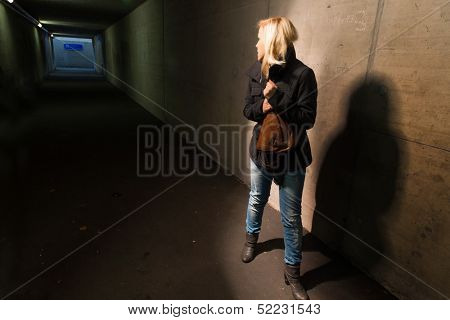 a young woman in an underpass for pedestrians is afraid of harassment and crime