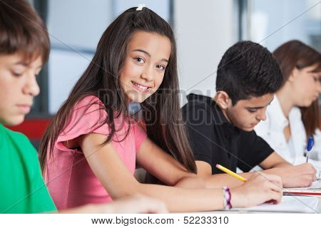 Portrait of happy teenage girl sitting with classmates studying at desk in classroom