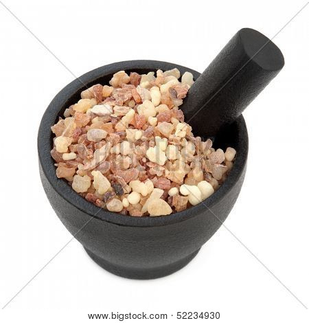 Frankincense and myrrh in a mortar with pestle and bowl over white background.