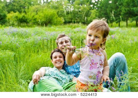 Toddler Eating Flower, Smiling Parents In Back