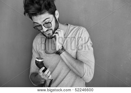 Sexy Man Rubbing His Beard Holding A Shaving Machine Against Wall